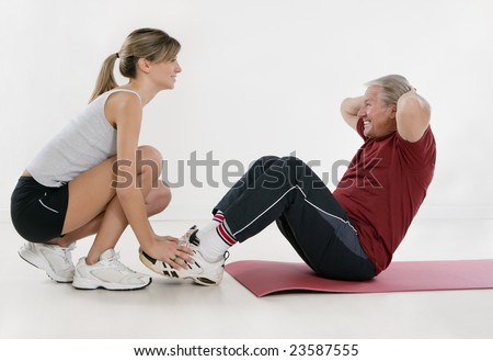 young personal trainer and senior adult exercising in gym - stock photo