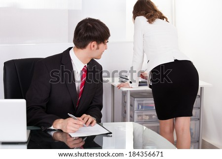 Young pervert businessman looking at businesswoman working in office - stock photo