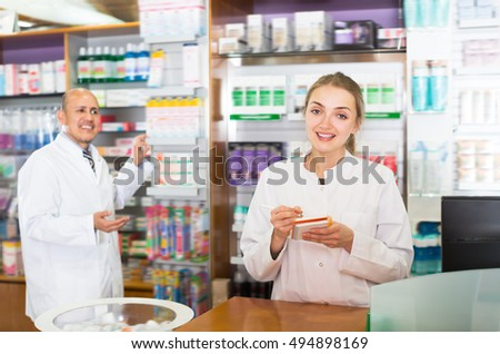 Young pharmacist and pharmacy assistant helping in drugstore
