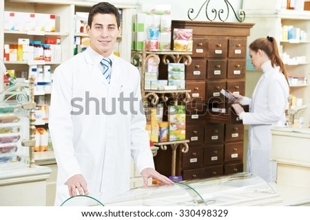 young pharmacist chemist man and woman  standing in pharmacy drugstore  - stock photo