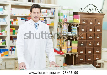 young pharmacist chemist man working in pharmacy drugstore with prescription - stock photo