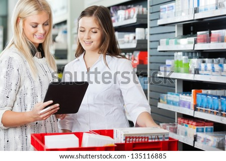 Young pharmacist helping customer in pharmacy with digital tablet - stock photo