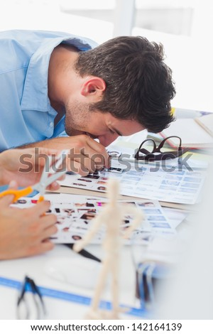 Young photo editor using magnifying loupe on a contact sheet - stock photo