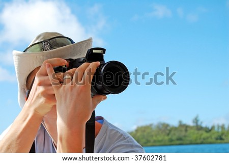 Young photographer aiming to take a shot - stock photo