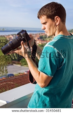 Young photographer checking new photographs on display of his digital slr camera. - stock photo