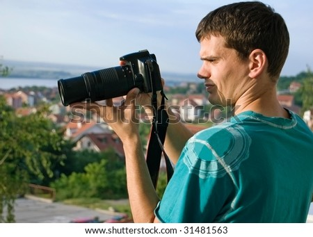 Young photographer checking new photographs on display of his digital slr camera - stock photo
