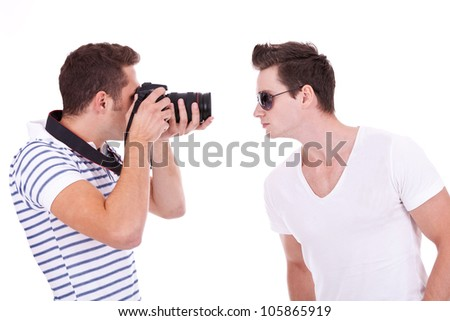 young photographer during a photo shoot with a male model, on white background - stock photo