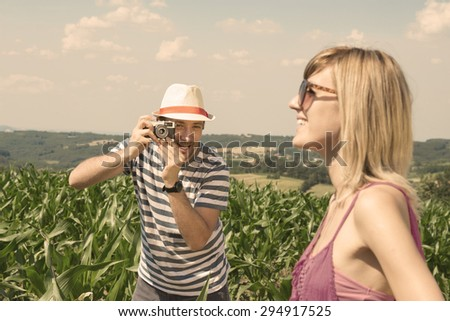 Young photographer finding the best position to take a shoot of his girlfriend � outdoor  - stock photo