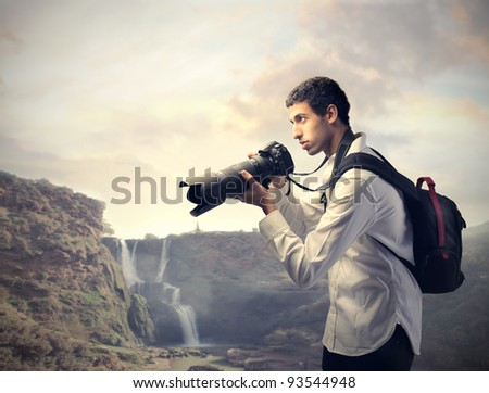 Young photographer holding a camera with landscape in the background - stock photo
