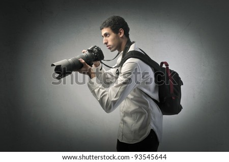 Young photographer holding a professional camera - stock photo