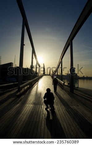 young photographer is getting ready for catching sunset in port vell on his camera. barcelona, spain