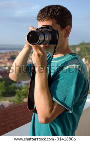 Young photographer is waiting for a good shoot - stock photo