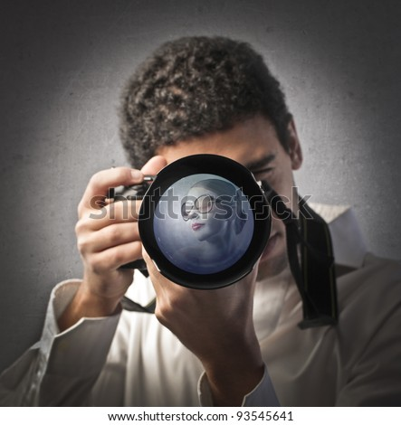 Young photographer looking through the lens of a camera with beautiful woman in it - stock photo