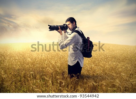 Young photographer on a wheat field - stock photo