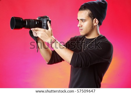Young photographer on red background - stock photo