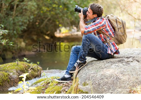 young photographer photographing in mountain valley - stock photo
