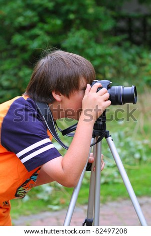 Young photographer takes pictures on the nature - stock photo