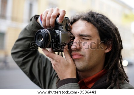 Young photographer taking a photo with DSLR camera - stock photo
