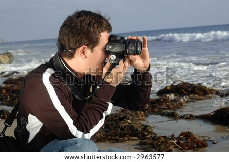 Young photographer taking a shot on the beach - stock photo