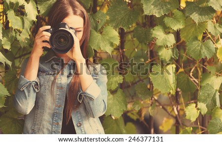 Young photographer taking photos outdoors - stock photo