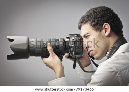 Young photographer taking pictures with a reflex camera - stock photo