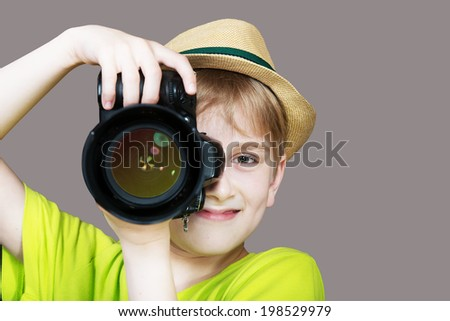 Young photographer with a camera pointing the lens directly at the viewer, gray background - stock photo