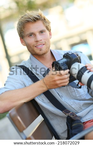 Young photographer with camera sitting on a bench