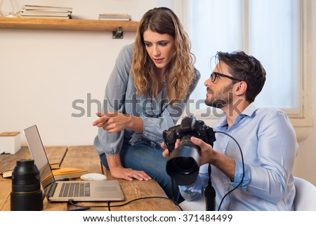 Young photographers looking at photographs on laptop. Assistant photographer helping photographer in the selection of photos. Young team of photographer working in a professional studio.