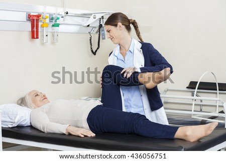 Young Physiotherapist Helping Senior Woman With Leg Exercise - stock photo