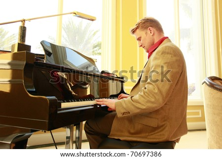 Young pianist at an afternoon lounge - stock photo