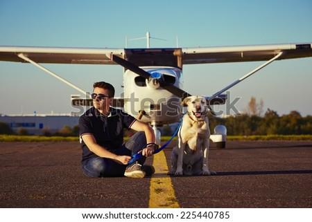 Young pilot with dog are sitting in front of the airplane - stock photo