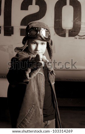 Young pilot with goggles pointing at the camera - stock photo