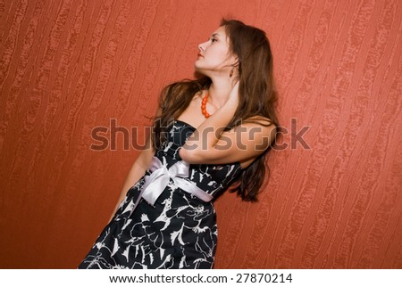 young pin-up girl in front of red wallpaper - stock photo