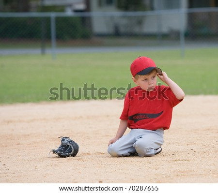 Young player sitting on infield during game. - stock photo