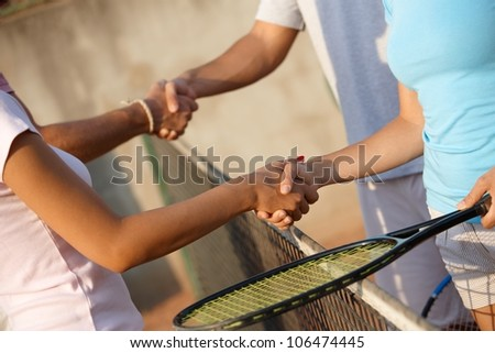 Young players shaking hands on tennis court, only hands can be seen. - stock photo