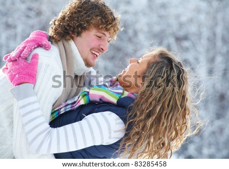 young playful couple has a fun winter time in a snow park