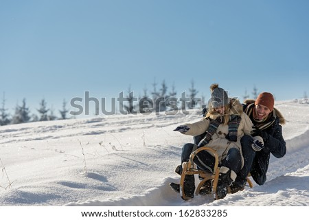 Young playful couple having fun in the snow sledging downhill - stock photo