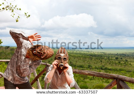 Young playful couple in African masks - stock photo