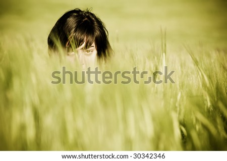 Young playful woman barely seen among the wheat - stock photo