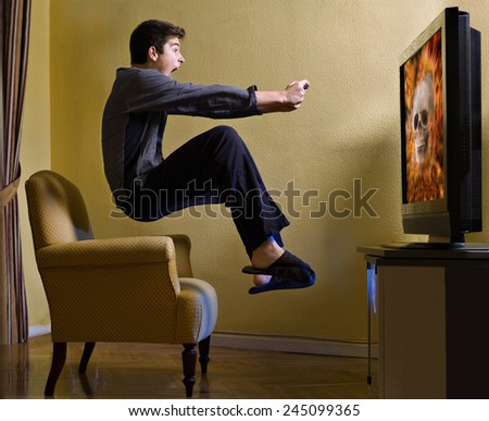 Young playing on TV with a video game, scared and in the air - stock photo