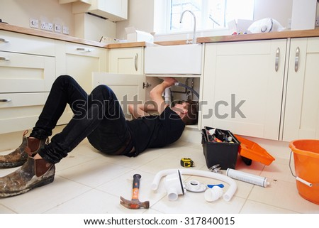 Young plumber at work under kitchen sink, tools in foreground - stock photo