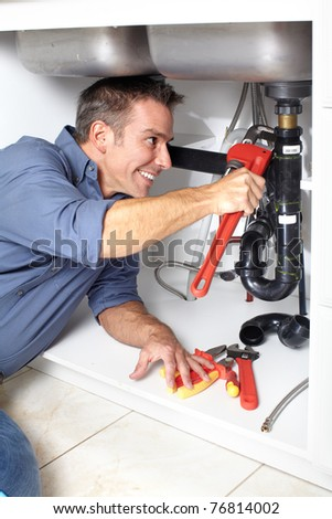 Young plumber fixing a sink at kitchen. - stock photo
