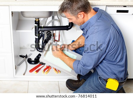 Young plumber fixing a sink at kitchen.