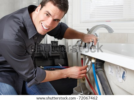 Young plumber fixing a sink. Worker at kitchen - stock photo