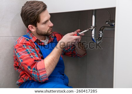 Young plumber is repairing a sink at the bathroom - stock photo