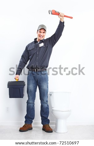 Young plumber near a flush toilet - stock photo