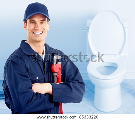 Young plumber near a flush toilet.
