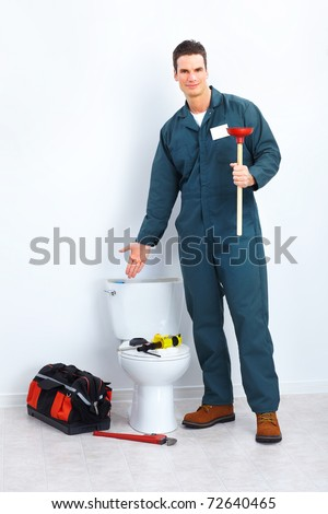 Young plumber releasing stoppage in the flush toilet - stock photo