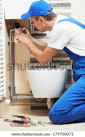 Young plumber worker working with spanner at sanitary washbasin installation system - stock photo