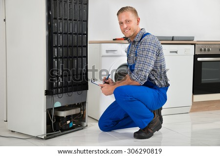 Young Plumber Writing On Clipboard In Front Of Refrigerator Appliance In Kitchen Room - stock photo